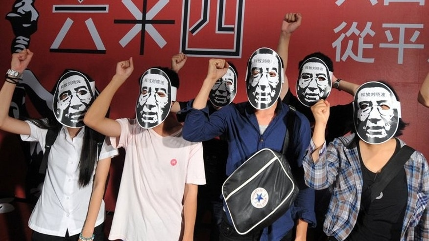 "Students wear Liu Xiaobo masks at a Tienanmen massacre commemoration in Taipei on June 4. Liu Xiaobo was jailed in 2009 for ""subversion"" after he circulated a charter calling for democratic reforms."