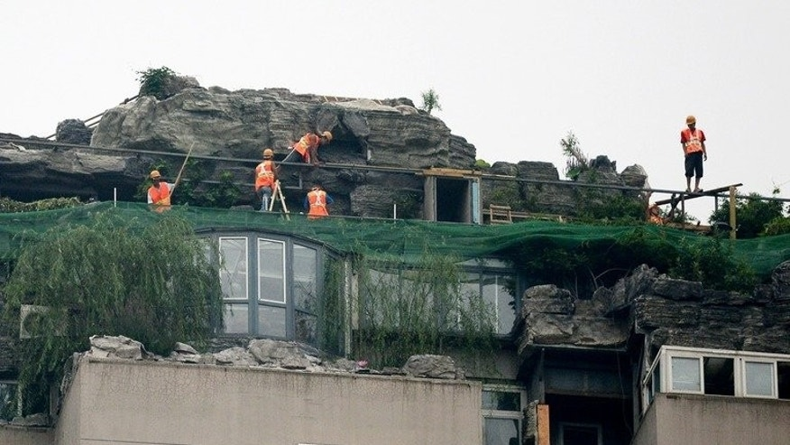 Workers demolish a bizarre villa and rock garden on the rooftop of a 26-storey apartment block in Beijing on August 16, 2013. A Beijing resident who built the structure on top the 26-storey building started dismantling it on August 15, after neighbours complained.