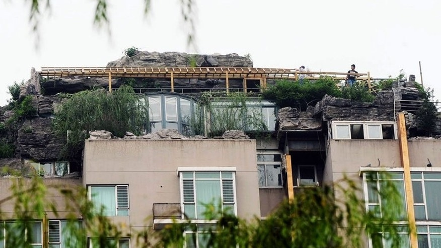 Two workers are seen demolishing the illegal rooftop on top of a Beijing apartment block on August 15, 2013. Authorities had given its owner 15 days to remove it or said it would be demolished.