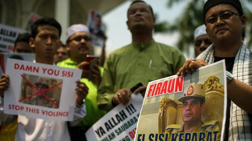 Malaysian Islamists hold placards during a rally at a mosque in Shah Alam, outside Kuala Lumpur on Friday. In the Malaysian capital Kuala Lumpur, about 500 Muslims protesters gathered after Friday prayers outside a major mosque in the suburbs to denounce the Egyptian crackdown.