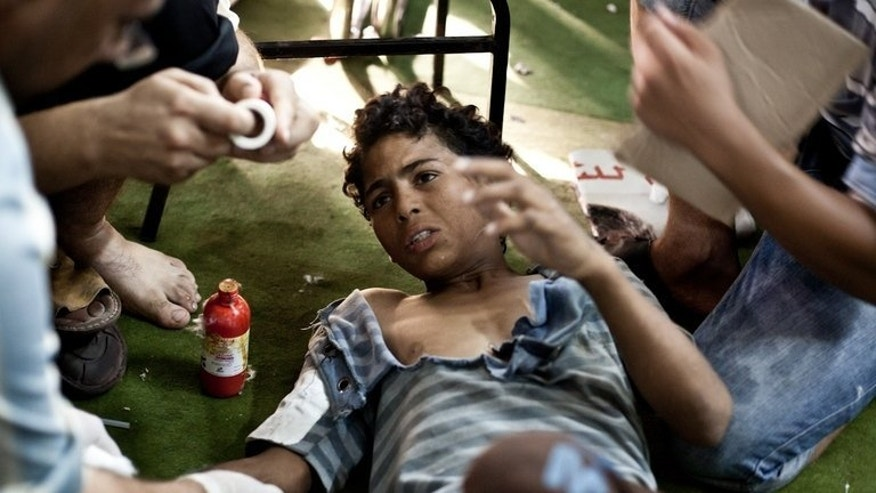 A wounded boy is treated as he lies on the floor of the Taamin Sehi field hospital during clashes between security officers and supporters of ousted president Mohamed Morsi, in Cairo, on August 16, 2013. The Egyptian cabinet described the unrest as a 'terrorist plot'.