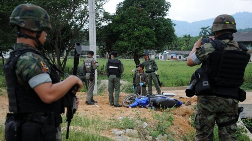 Bomb squad members inspect the site of a roadside bomb attack in Narathiwat province on Thursday. Four police officers were killed in a gun and grenade attack in front of a nursery school in Thailand's insurgency-hit south Friday, an official said, as bloodshed continued to dampen hopes for peace talks.