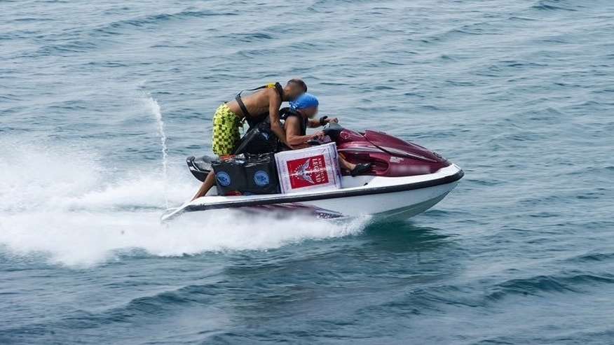 Two men on a jet ski smuggle contraband tobacco in Spain from Gibraltar on August 14, 2013. Widespread smuggling of cigarettes from the tiny, low-tax British outpost to Spain is one more irritant in their frayed diplomatic relations.