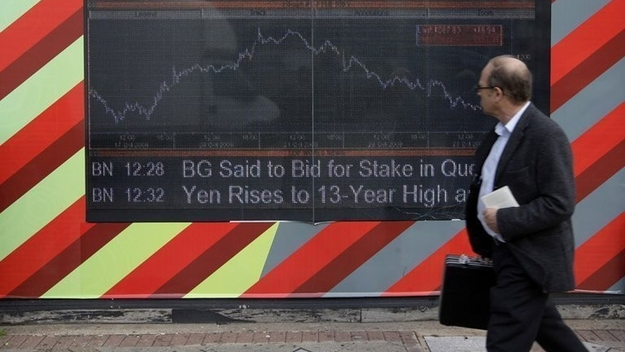 A man walks past an electronic display board showing the FTSE 100 share index in London on October 24, 2008. Shares in London were little changed on Friday amid low volumes, the benchmark FTSE 100 index edged up 0.02 percent to 6,484.43 points.
