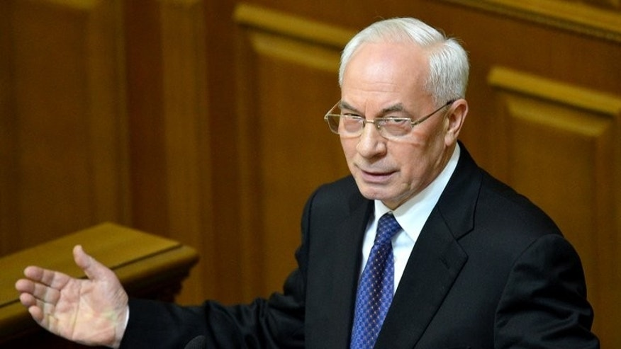 "Ukraine's Prime Minister Mykola Azarov delivers a speech at the Ukrainian parliament, in Kiev, on December 13, 2012. Azarov acknowledged ""difficulties"" at the border with Russia on Thursday but urged the media not to play up the scale of the dispute."