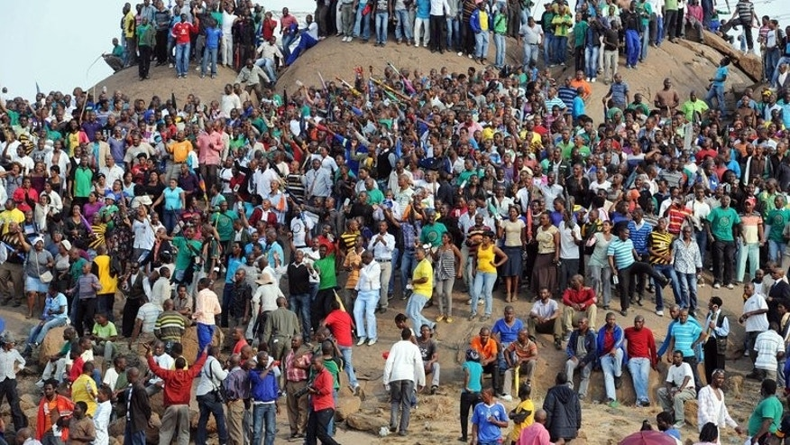 People gather on a hill in Marikana after attending a memorial service for the 44 people killed in a wildcat strike at Lonmin's Marikana mine, on August 23, 2012. South Africa on August 16 mark a year to the shocking massacre, faced with a fragile economy, tainted government and a disquiet labour force.