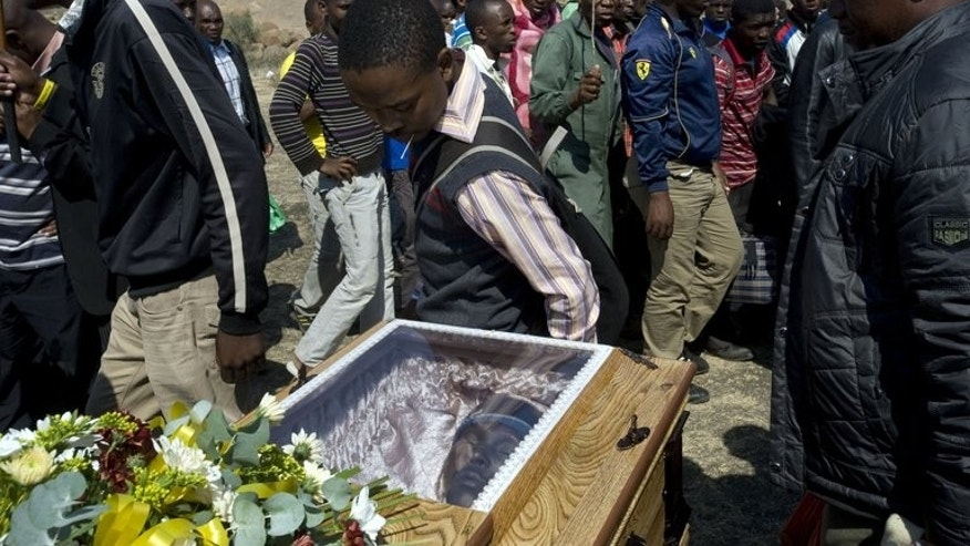 Lonmin mine-workers pay their last respects in front of a coffin containing the body of Mpuzeni Ngxande, one of the 34 striking miners that was killed by the police on August 16, in front of the rocky outcrop where the men were shot, near the Lonmin mine in Marikana, on August 31, 2012. South Africa on August 16 marks a year since the shocking massacre.