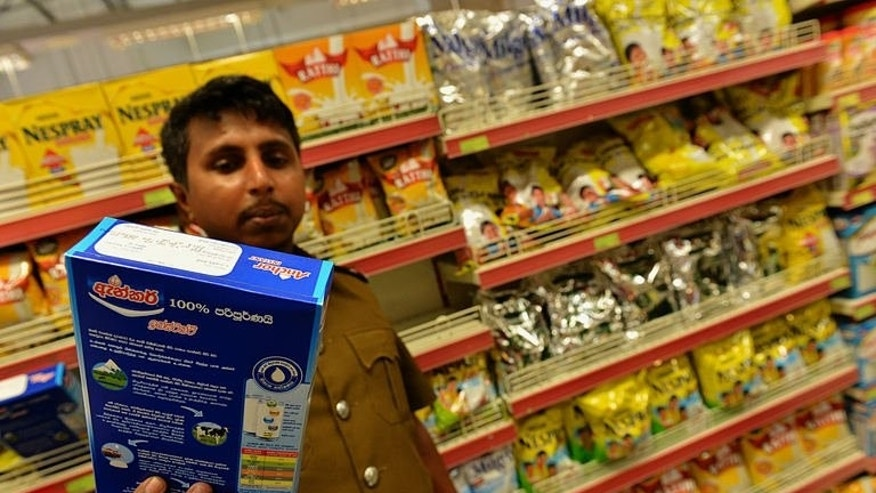 A Sri Lankan health inspector checks the batch code of a milk powder package in the capital Colombo on August 15, 2013. A Sri Lankan court Friday temporarily banned the sale and distribution of all milk products made by the New Zealand dairy giant Fonterra, which is under pressure over a global botulism scare.