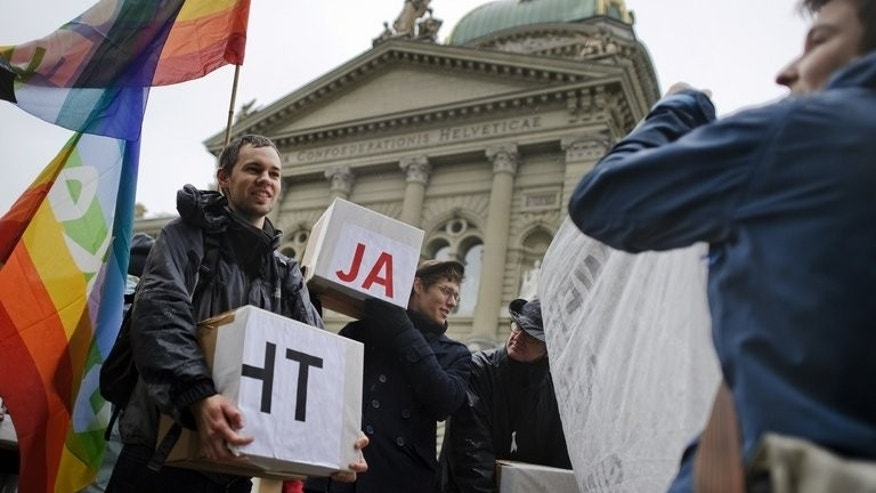Members of the group for Switzerland Without an Army hold boxes with signatures collected for a popular initiative to end military conscription, outside of the Swiss House of Parliament on January 5, 2012 in Bern. The Swiss government on Friday urged voters to maintain the country's compulsory military service when they head to the polls next month for a referendum on the issue.