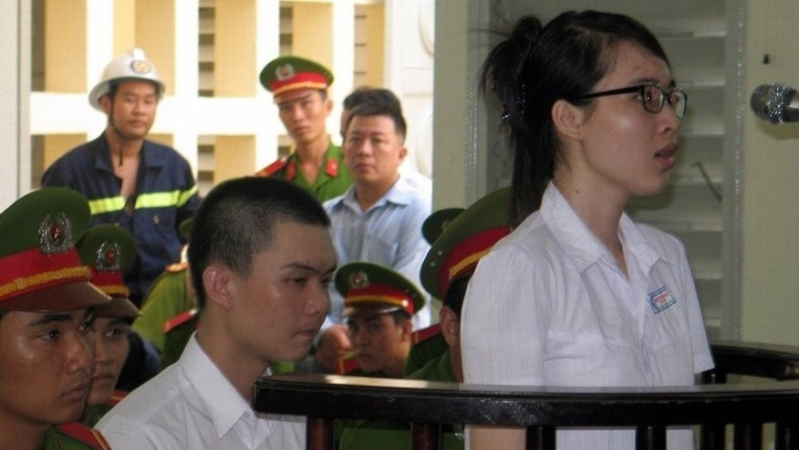 Nguyen Phuong Uyen (right) and Dinh Nguyen Kha stand trial in the southern province of Long An on May 16. A Vietnamese court on Friday overturned a six-year jail term handed to a student activist, freeing her on the spot in a rare show of leniency by the authoritarian nation.