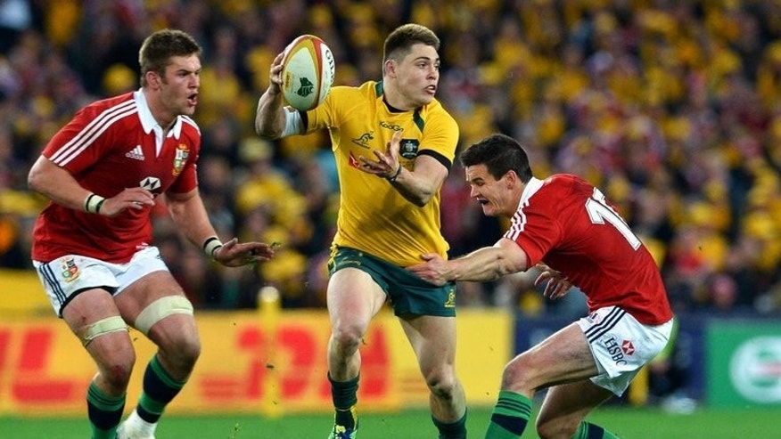 Australia's James O'Connor (C) attempts to break through British and Irish Lions defenders Dan Lydiate (L) and Jonathon Sexton on July 6, 2013. Australia face the All Blacks in Saturday's Bledisloe Cup Test.