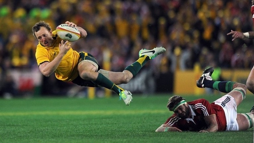 Australia's Jesse Mogg (L) attempts to break a tackle during the Test against the British and Irish Lions in Sydney on July 6, 2013. Team vice-captain Will Genia said Mogg was 'incredibly quick' and he will add to the Wallabies' counter-attacking capability.