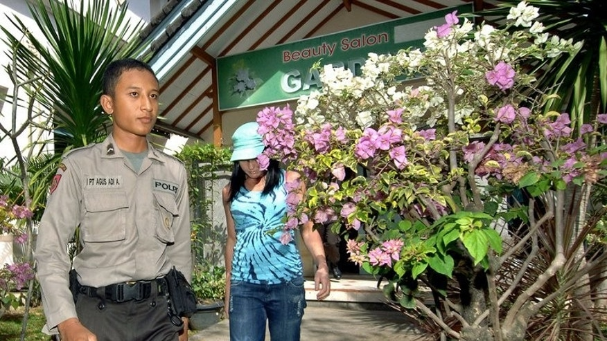 Convicted Australian drug trafficker Schapelle Corby (R) is escorted a policeman as she leaves a beauty salon in Denpasar on Bali island on July 2, 2008.