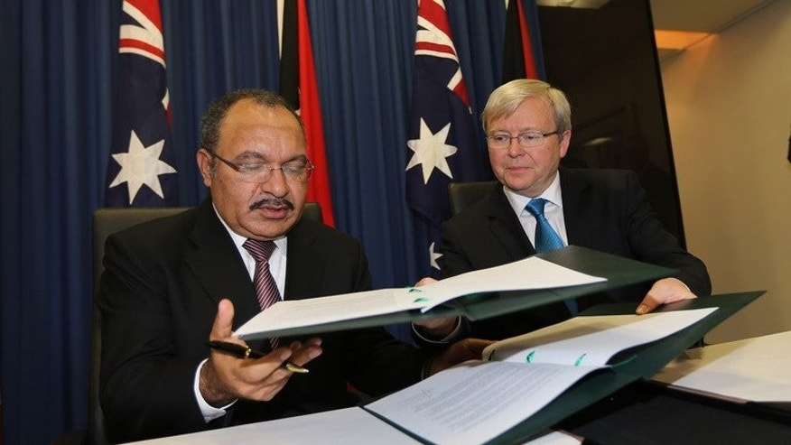 Australian Prime Minister Kevin Rudd, (R) and Papua New Guinea's Prime Minister Peter O'Neill exchange documents after signing an agreement during an announcement of a policy on asylum seekers in Brisbane on July 19, 2013.