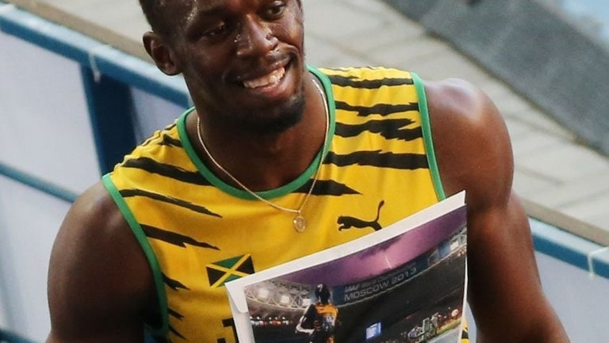 "Jamaica's Usain Bolt poses with an AFP picture by photographer Olivier Morin in Moscow on Friday. Bolt said an AFP photograph of the sprinter clinching world 100m gold as a lightning bolt illuminated the stormy skies above was ""amazing""."