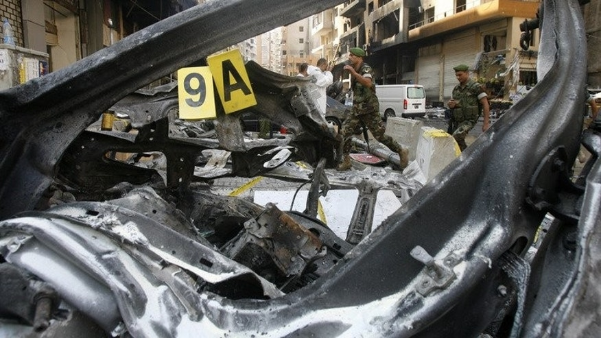Soldiers walk behind a burnt vehicle as they work on the scene of the previous day's car bomb explosion in southern Beirut on August 16, 2013. The death toll has risen to at least 27, the health ministry said Saturday.