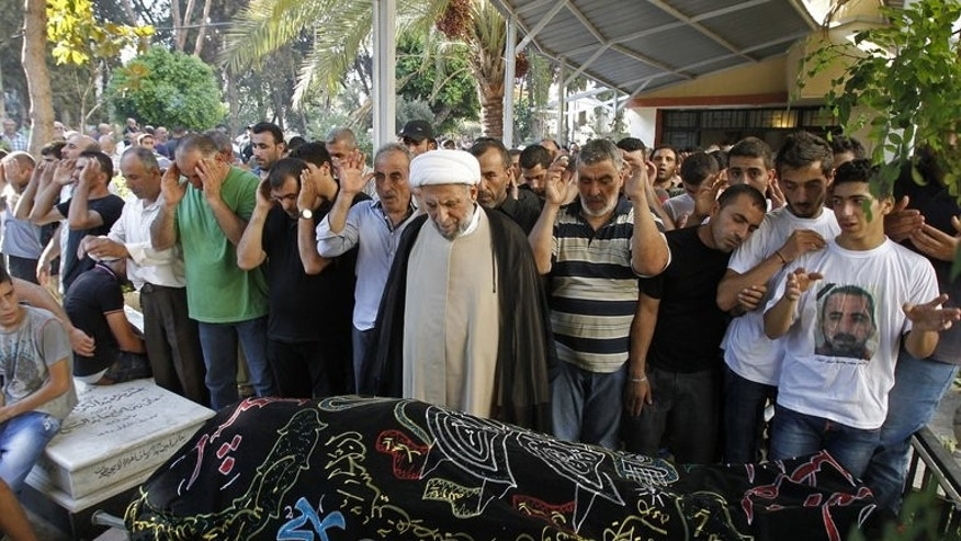 Mourners pray over the body of Hamad al-Moqdad, one of the Lebanese victims of a car bomb attack that killed dozens in a Beirut stronghold of Shiite group Hezbollah, during his funeral procession in the capital on August 16, 2013.