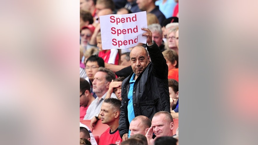 An Arsenal fan holds up a poster bearing the message 'spend, spend, spend' to Arsenal's Arsene Wenger on August 17, 2013. Wenger said the team was 'ready to buy players', despite only one newcomer this season.