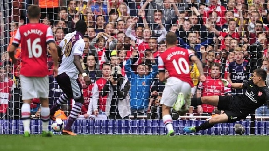 Aston Villa striker Christian Benteke (2L) slots home a penalty past Arsenal keeper Wojciech Szczesny (R) on August 17, 2013. Two goals from Christian Benteke and a late effort from new signing Antonio Luna secured Villa's victory.