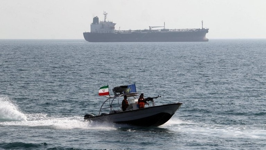 Iranian Revolutionary Guards drive a speedboat in front of an oil tanker at the port of Bandar Abbas on July 2, 2012. New Delhi and Tehran were Saturday working to resolve a dispute over the detention of an Indian oil tanker by Iranian naval guards for allegedly polluting sea waters in the Persian Gulf.