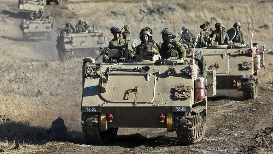 Israeli army Armored Personnel Carriers maneuver during a military exercise near the northern border with Syria on June 25, 2013. The Israeli army fired into Syria after shells from the neighbouring country hit the Israeli-occupied sector of the Golan Heights on Saturday, a military spokesman said.