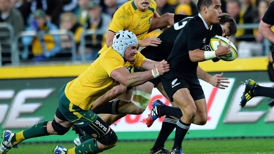 Australia's Ben Mowen (L) tackles Aaron Smith of New Zealand in Sydney on August 17, 2013. The World Cup champions trounced Australia despite the Wallabies' manager's talk of a fresh approach.