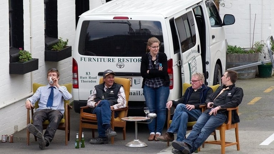 Workers sit outside prefering not to return to old workshops after a 6.5 earthquake hit central New Zealand on August 16, 2013. The powerful earthquake rattled major cities across the country, terrifying residents.