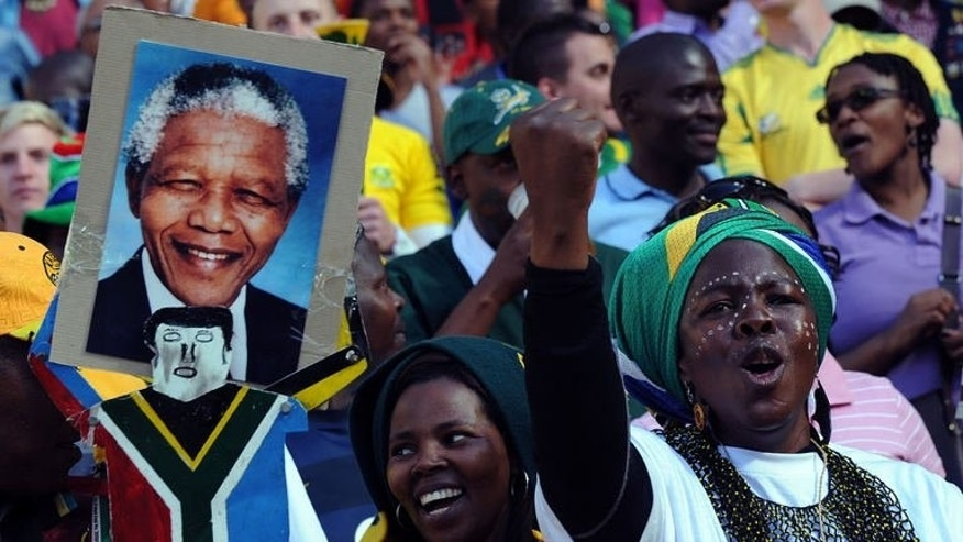 South Africa's football fans celebrate a win over Burkino Faso during the Nelson Mandela Sports and Culture Day in Soweto at FNB Stadium on August 17, 2013.