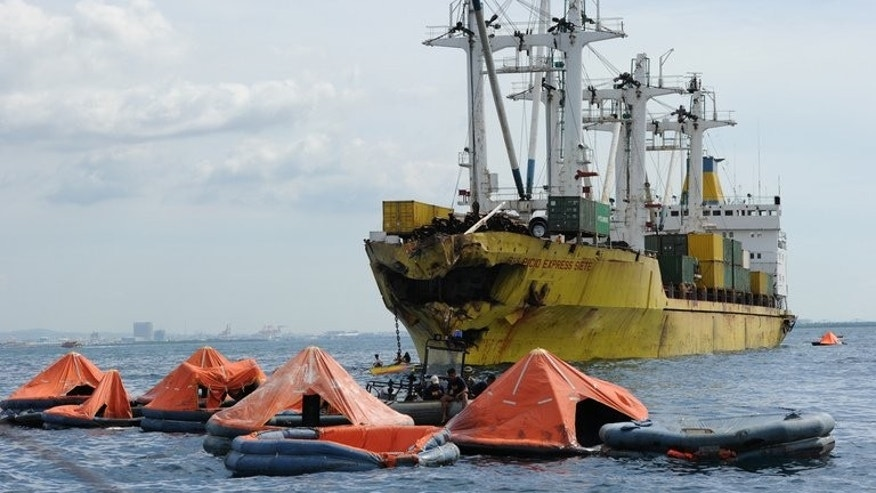 Life rafts from the sunken ferry St. Thomas Aquinas float in front of a cargo ship on August 17, 2013. Rescuers continued their afforts on August 18, but were hindered by rough seas.