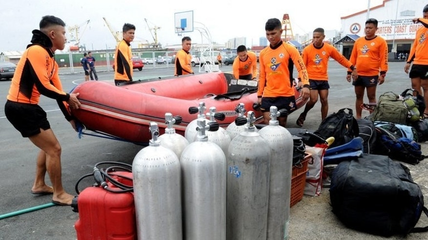 Philippine Coast Guard divers unload a rubber boat as they prepare join rescue operations in Cebu from their headquarters in Manila on August 17, 2013. Thirty-two people are confirmed dead, with 170 missing following the sinking of a ferry.