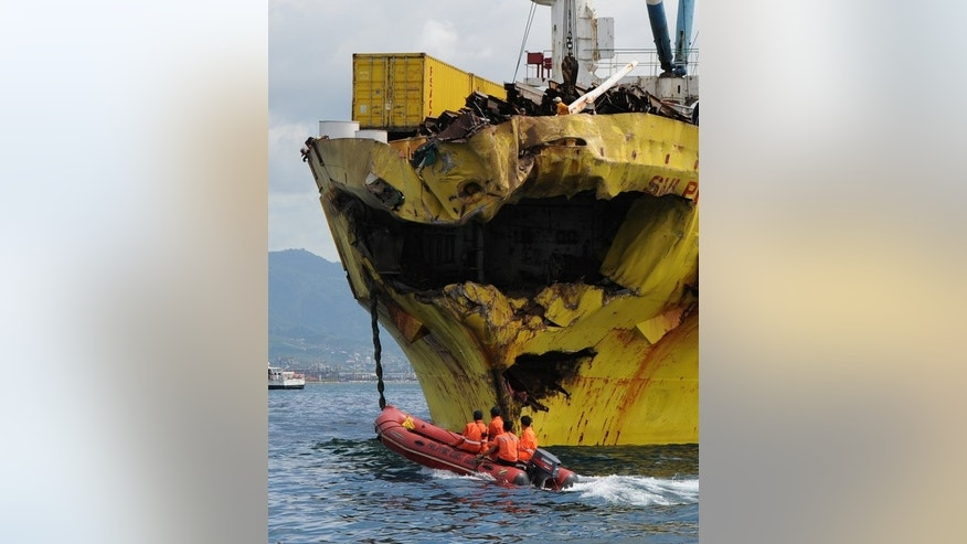 Philippine Coast Guard personnel ride a rubber dingy to inspect the damaged bow of a cargo ship on August 17, 2013. Rescuers said there was still a slim chance people could be alive in the sunken ferry.