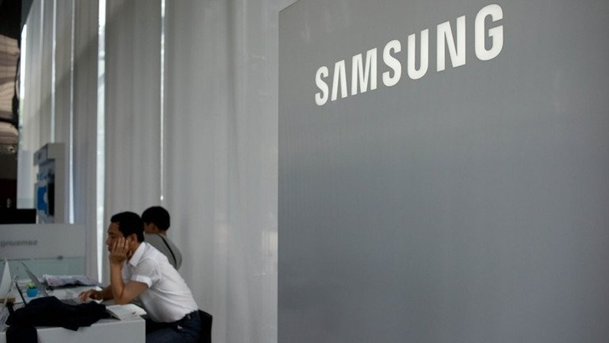 "A Samsung logo is displayed at a showroom in Seoul on July 5, 2013. South Korea's Samsung Electronics will unveil its new Galaxy Gear ""smartwatch"" early next month, ahead of Apple's iWatch, Bloomberg news and a fan site said Saturday."