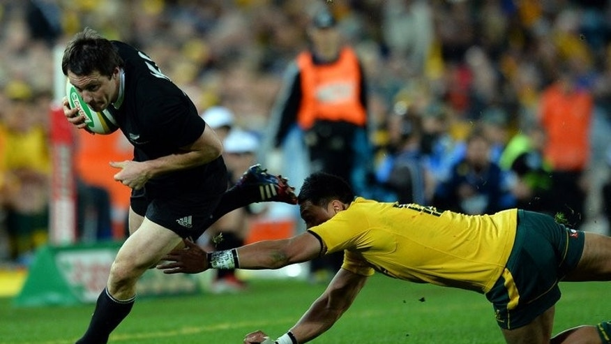 Ben Smith (centre) runs for a try after evading Australia's Will Genia in Sydney on Saturday. Winger Smith became the first All Black to score a hat-trick of Test tries in eight years with other tries to skipper Richie McCaw, Aaron Cruden and Conrad Smith.