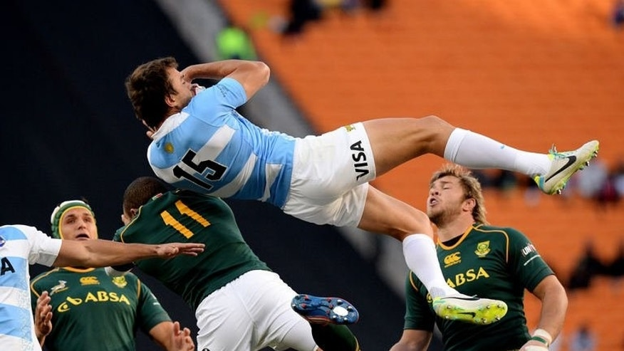 Argentinian rugby player Juan Martin Hernandez (C) jumps for the ball during a Rugby Championship first round match between against South Africa at the Soccer City stadium in Soweto, on August 17, 2013. South Africa scored nine tries and fly-half Morne Steyn kicked 28 points as they crushed Argentina 73-13 Saturday in a Rugby Championship first round romp.