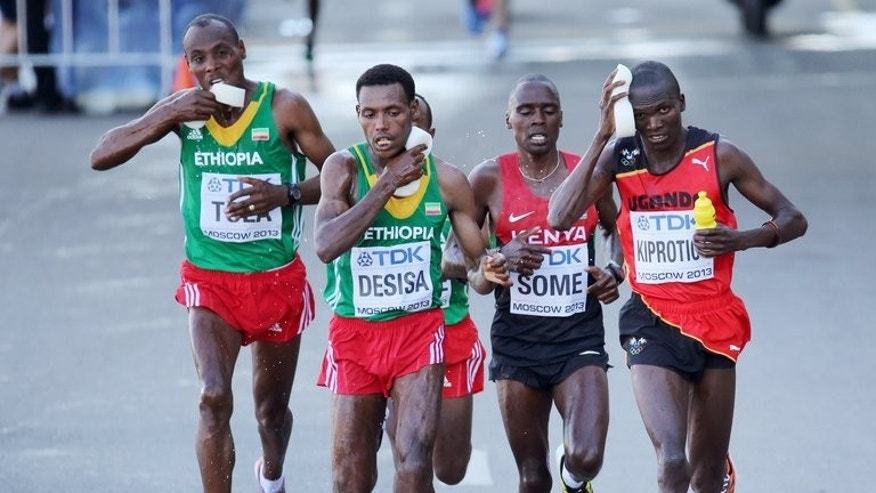Stephen Kiprotich (right) cools himself down during the World Championsip marathon in Moscow on Saturday. The Ugandan prison warden clocked 2hr 09min 51sec around the streets of Moscow, with Ethiopian duo Lelisa Desisa (2nd left) and Tadese Tola (left) claiming silver and bronze respectively.