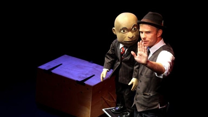 Comedian Conrad Koch gestures with his puppet Chester Missing during a performance at the Market Theatre in Johannesburg on May 7, 2013. The black puppet and its white comedian master have joined a growing group of no-holds-barred jokesters who slaughter the country's holy cows like racism and the ruling African National Congress (ANC).