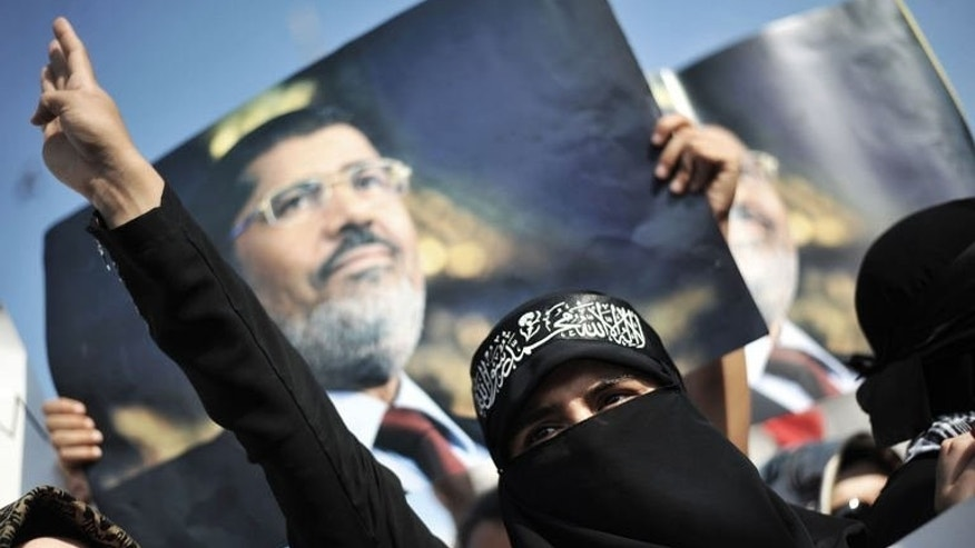 A protestor chants slogans in front of a poster of Egypt's ousted president Mohamed Morsi at a demonstration against violence in Cairo on August 17, 2013, at New Mosque in Istanbul. European Union leaders Herman Van Rompuy and Jose Manuel Barroso warned Egypt's army and interim government Sunday the bloc would review its ties with the country unless the violence ended.