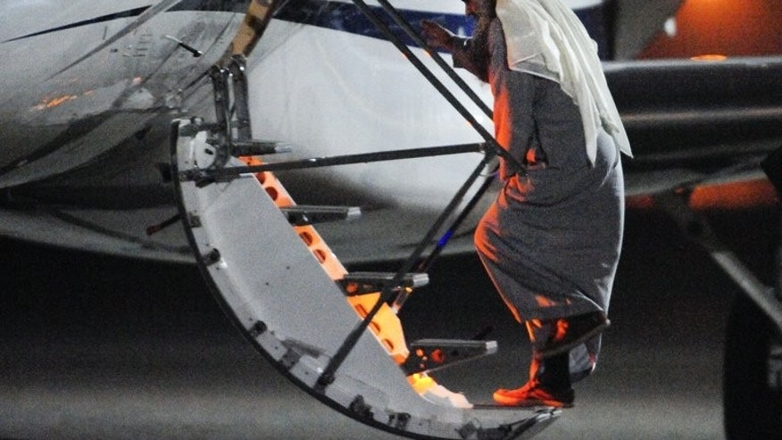 Radical Islamist cleric Abu Qatada boarding a privately chartered jet at the RAF Northolt base in west London on July 7, 2013, as he gets deported to Jordan. The family of the radical cleric, who faces terror charges in Jordan following his deportation from Britain, has arrived in the Arab kingdom, his brother said on Sunday.