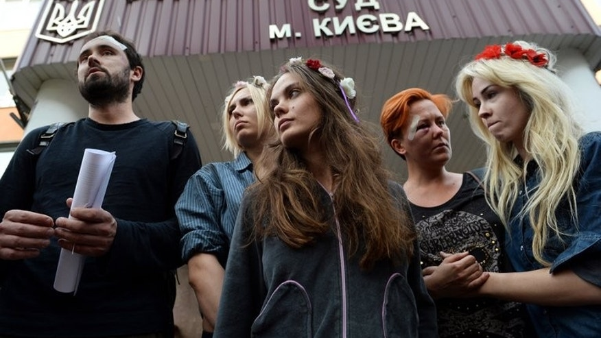 Femen activists Yana Zhdanova, Oksana Shachko, Anna Hutsol and Oleksandra Shevchenko leave the district court in Kiev on July 28, 2013. The head of the Ukrainian feminist movement Femen alleged Sunday that she and two other activists of the group known for its topless protests were beaten by special forces.