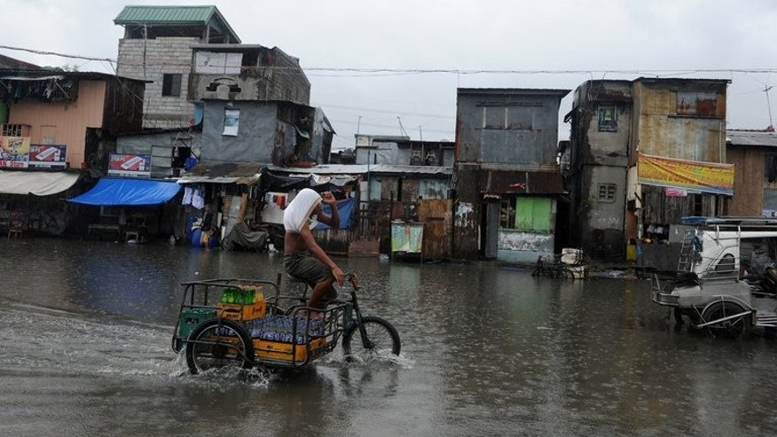 A man on his bike wades through a flooded street in Manila on June 30, 2013. Fresh flooding paralysed parts of the capital on Monday after heavy rain overnight from Tropical Storm Trami.