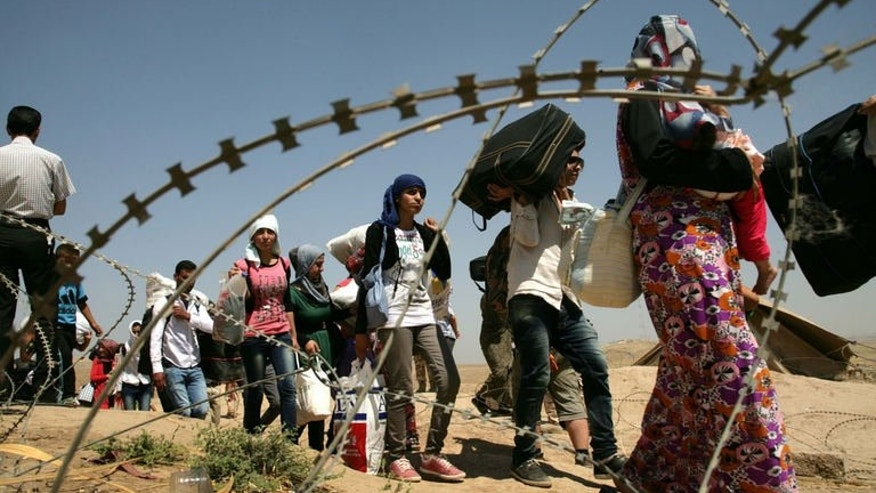 Syrian refugees cross the border into the autonomous Kurdish region of northern Iraq, on August 17, 2013. Faced with brutal violence and soaring prices, thousands of Syrian Kurds have poured into Iraq's autonomous Kurdish region, seeking respite from privation and fighting between Kurdish fighters and jihadists.