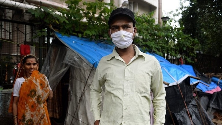 A cancer sufferer stands outside his temporary shelter on the pavement outside the Tata Memorial hospital in Mumbai, on August 1, 2013. Patients seeking treatment at the over-crowded hospital are forced to deal with rats, mosquitoes and dirt.