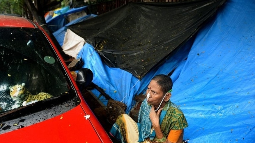 An Indian cancer patient sits on the pavement near a temporary shelter set up outside the Tata Memorial hospital in Mumbai on August 1, 2013. With just a patchwork of colourful plastic sheets to shield patients from the heavy monsoon rains, a Mumbai street acts as an unofficial ward to one of India's top cancer treatment centres.