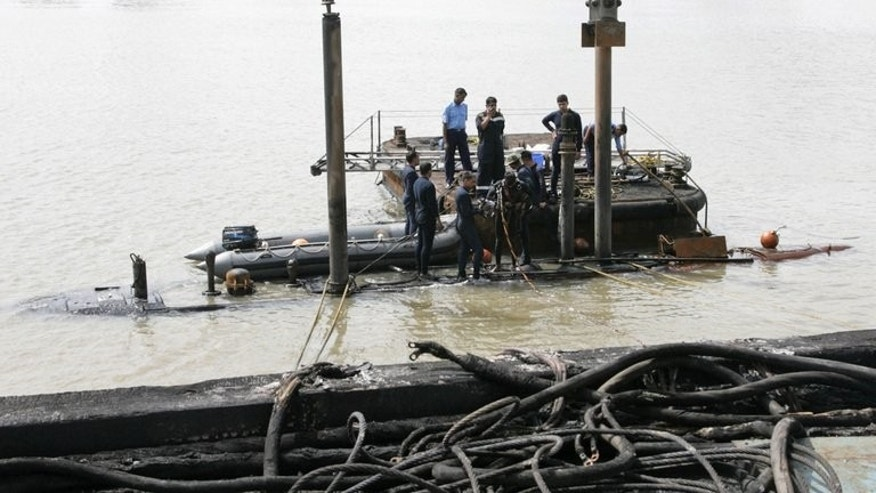 In this handout photograph released by the Ministry of Defence and taken on August 14, 2013, Indian Navy divers are pictured at the conning tower of the stricken INS Sindhurakshak, after the submarine sank following an explosion at the naval dockyard in Mumbai. Divers have recovered another burnt body from a submarine that exploded in Mumbai as they battled to find 12 remaining crewmen.