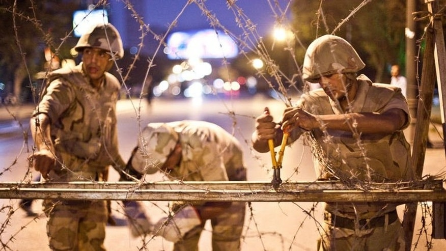 Egyptian army soldiers take out barbed wire that was surrounding the Supreme Constitutional Court in Cairo ahead of planned demonstrations on August 18, 2013. Iraq's premier backed the Egyptian military crackdown on supporters of ousted president Mohamed Morsi in a statement Sunday, the latest Arab leader to back the operation.