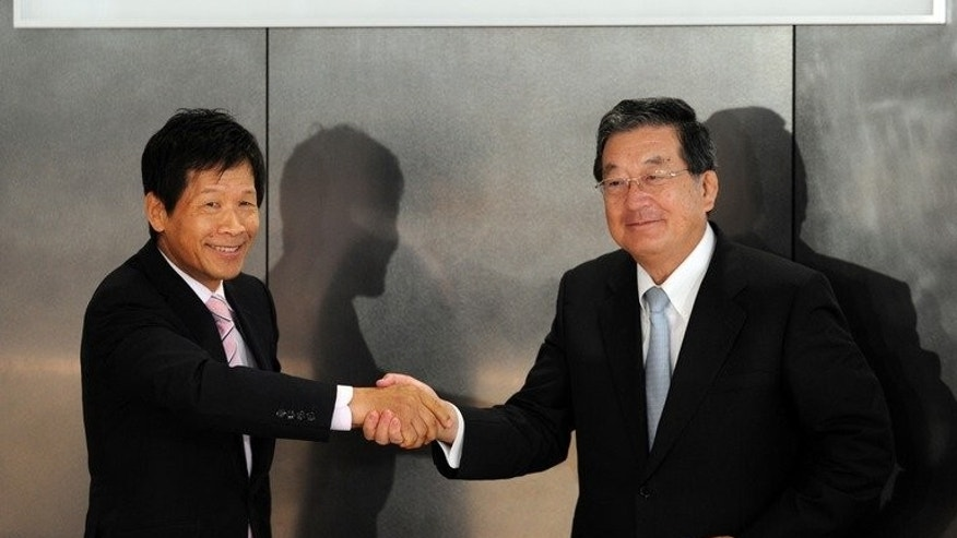 Illustration: Nippon Steel and Sumitomo Metal chairman and CEO Shoji Muneoka shakes hands with president Hiroshi Tomono as they unveil the company's plaque in Tokyo on October 1, 2012. Nippon Steel, which last year merged with Sumitomo, is being sued by four South Korean wartime slave workers.