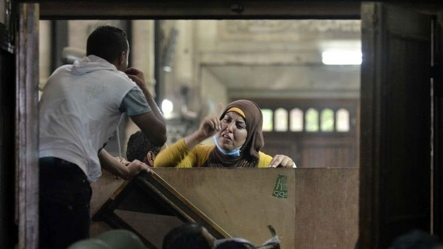 An Egyptian woman talks to policemen from the inside of Cairo's Al-Fath mosque where Islamist supporters of ousted president Mohamed Morsi held up on August 17, 2013. Qatar's foreign minister said Monday his country had never given aid to Egypt's Muslim Brotherhood and that all assistance went to Egypt as a whole.