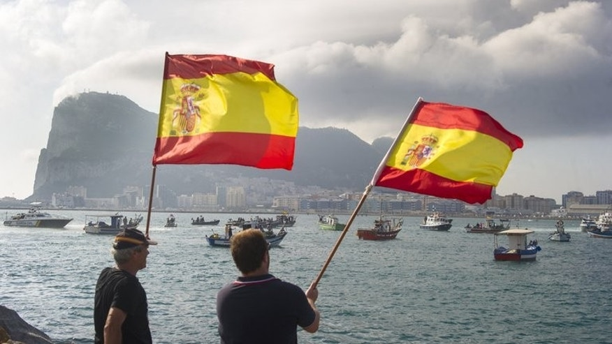 Fishermen wave Spanish flags during a protest in the bay of Algeciras on Sunday. Dozens of Spanish fishing boats sailed to Gibraltar on Sunday to demand that the British outpost remove 70 concrete blocks it has dropped in their fishing grounds.