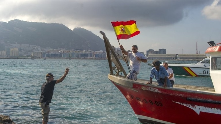 A fisherman holds a Spanish flag during a protest in the bay of Algeciras on Sunday. The Spanish fishermen from the nearby ports of La Linea de la Concepcion and Algeciras set sail on calm waters across the narrow strait, accompanied by a half dozen Spanish police patrols.