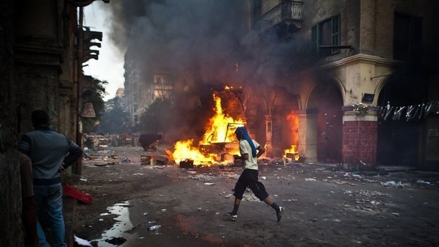 "A supporter of the Muslim Brotherhood runs past a burning vehicle near Cairo's Ramses Square, on August 16, 2013 . Just two years ago, Egypt's Muslim Brotherhood won the country's first free elections, but now many in the country call its supporters ""terrorists."""